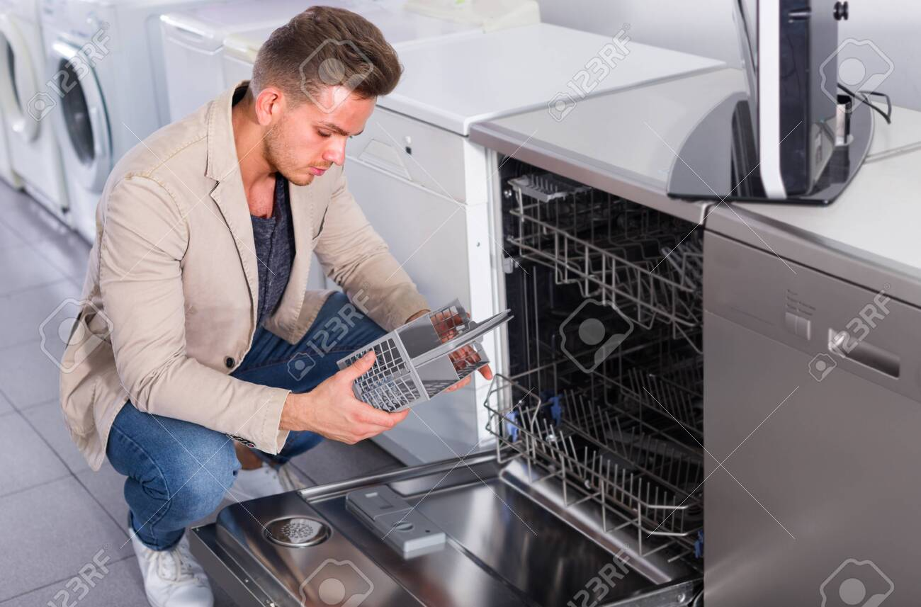Male customer looking at dishwashers in domestic appliances store indoors - 120937198