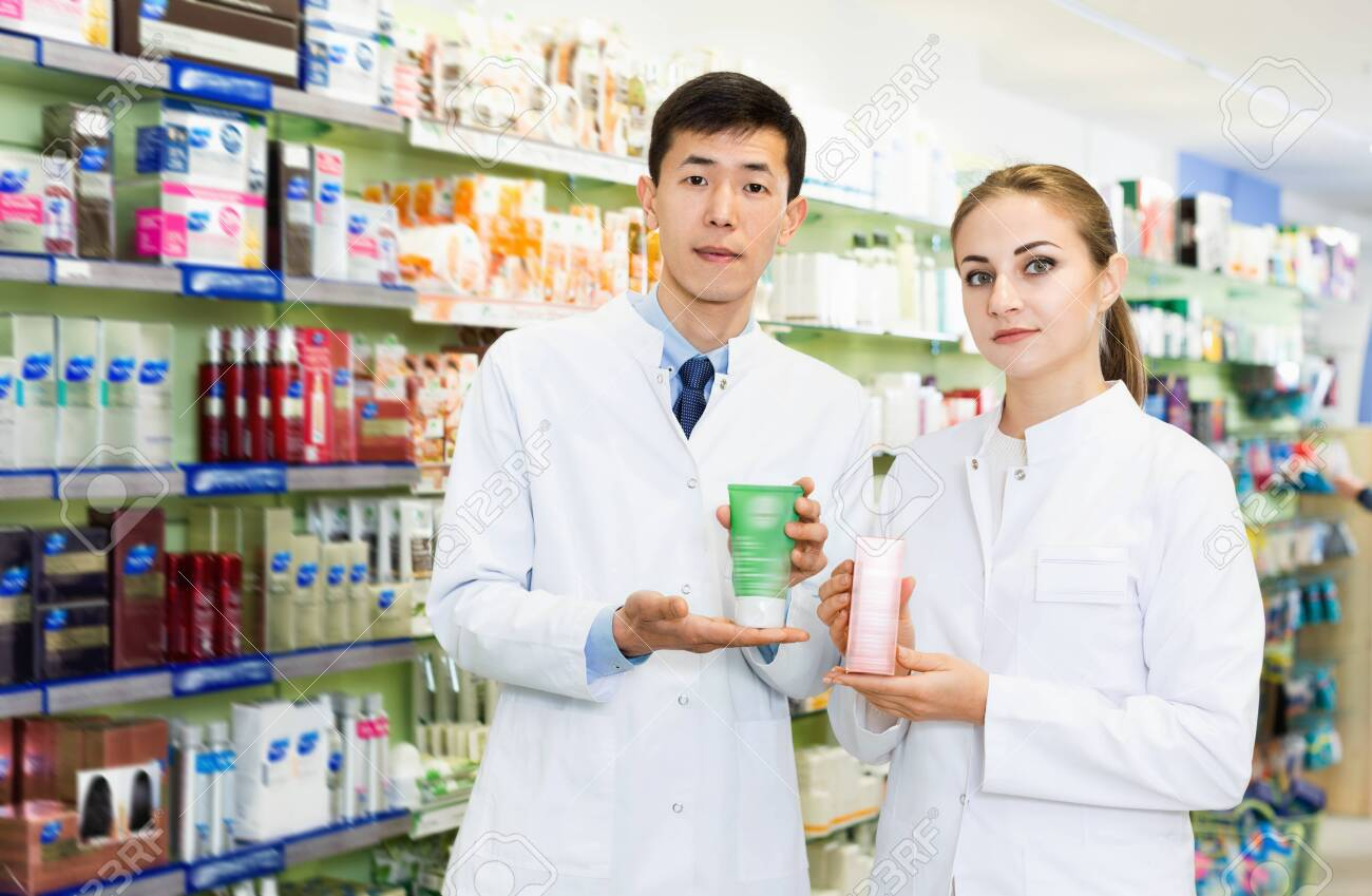 Twodiligent serious specialists are holding medicines and standing in hall of pharmacy. - 121088324