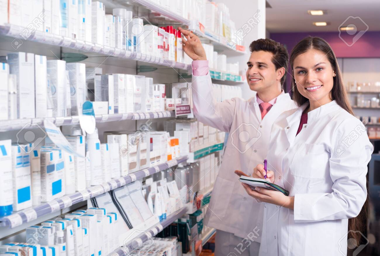 Smiling pharmacist and pharmacy technician posing in interior - 121964538