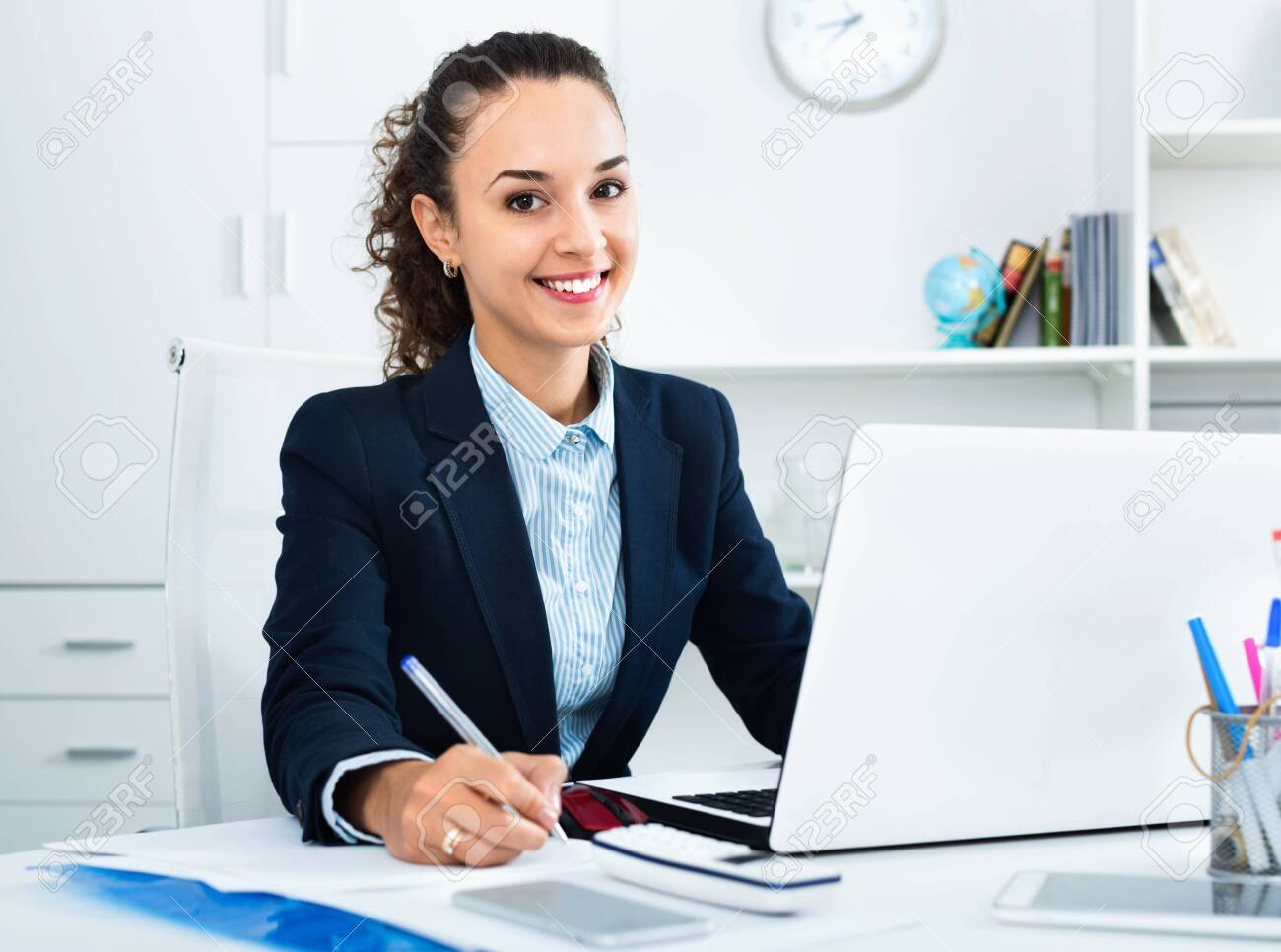 Positive pleasant business lady sitting at office desk with laptop - 122045531