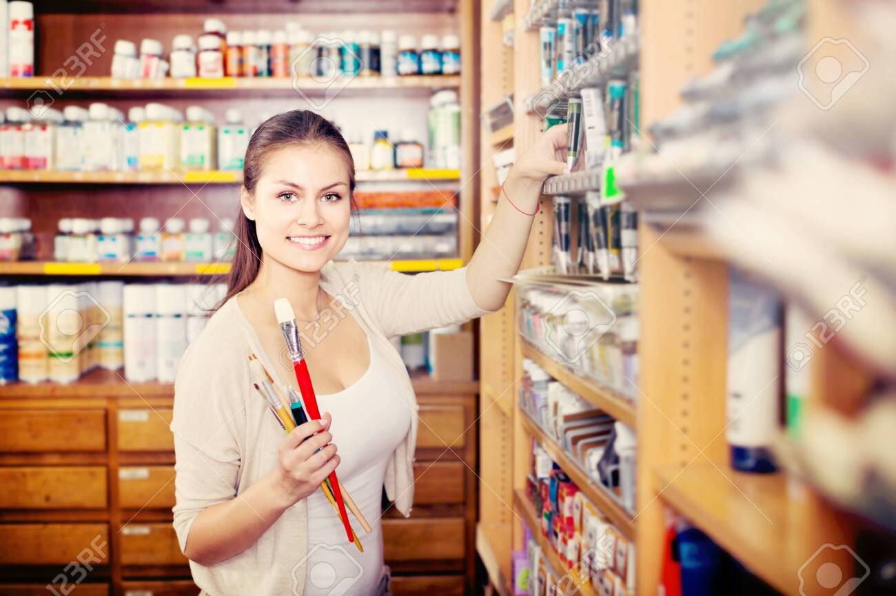 portrait of young cheerful woman choosing paint color in tube in art shop - 122045717