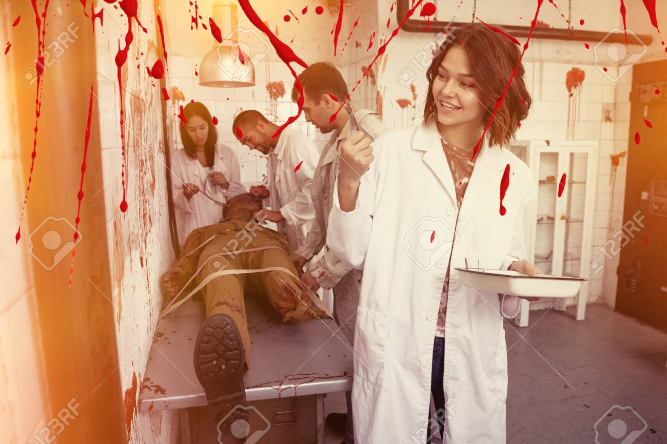 Smiling girl spending time with friends in closed space of lost room with bloody walls and zombi on table - 122507563