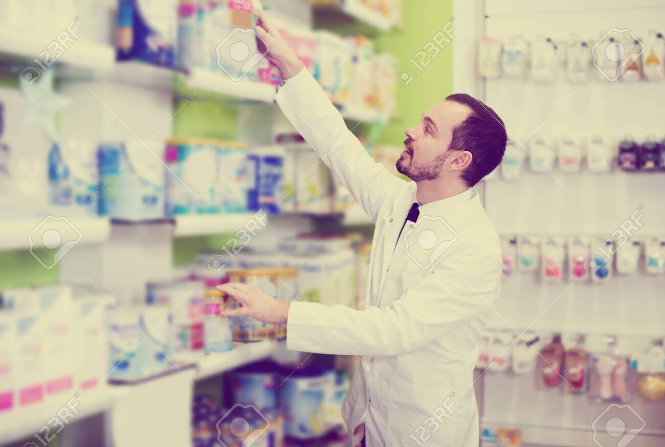 Glad man pharmacist searching for reliable drug in pharmacy - 123334808