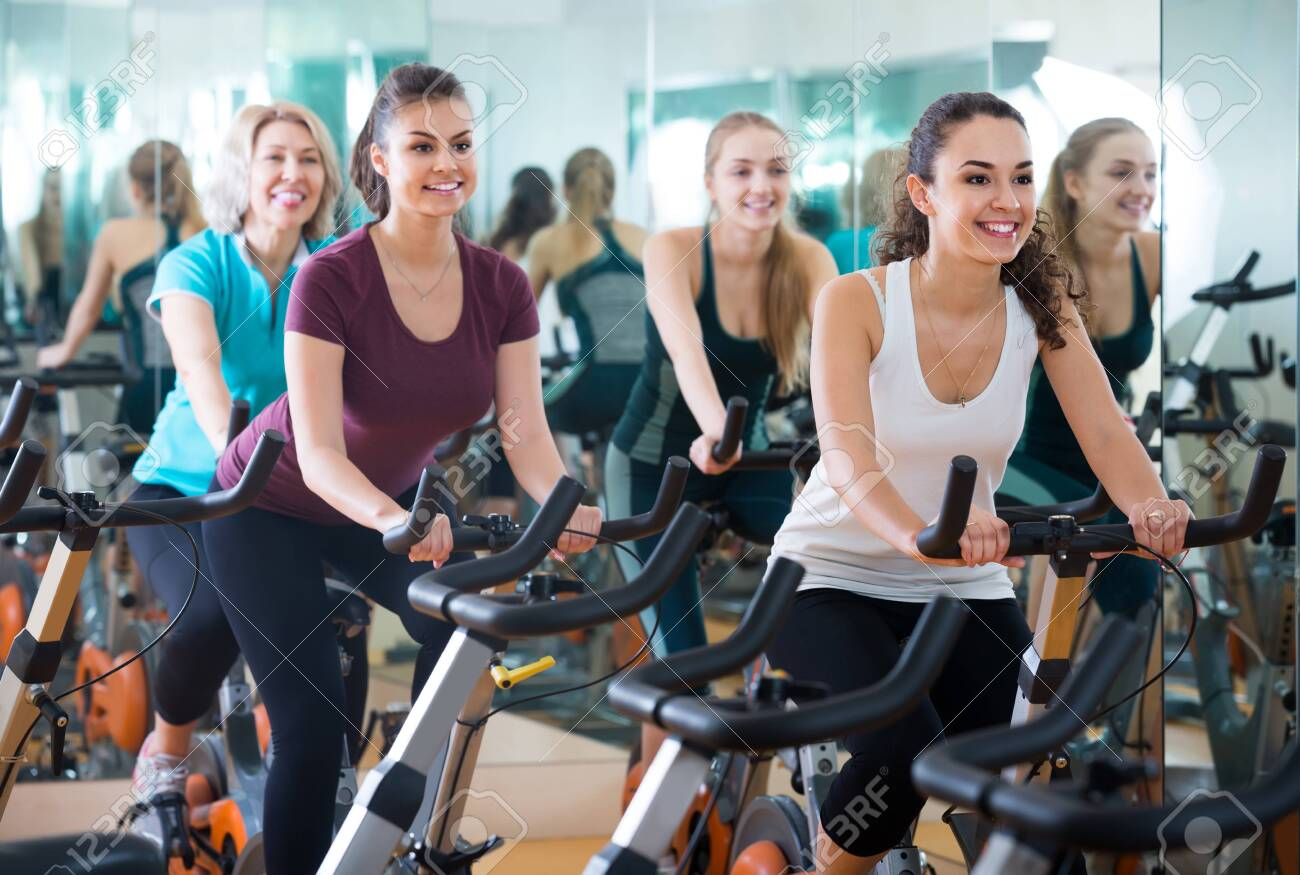 Brunette smiling european girl and other females working out in sport club - 123765886