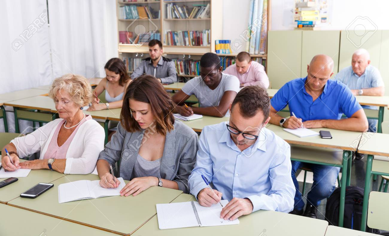 Glad students mixed age listening task for exam in the classroom - 124779527