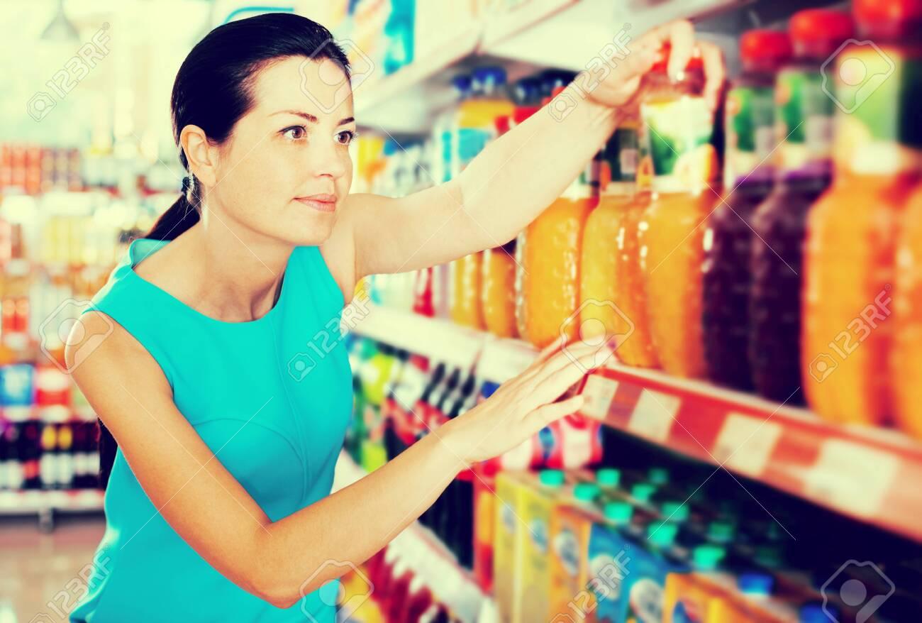 Attractive young woman choosing fruit juice on supermarket shelf - 124370404
