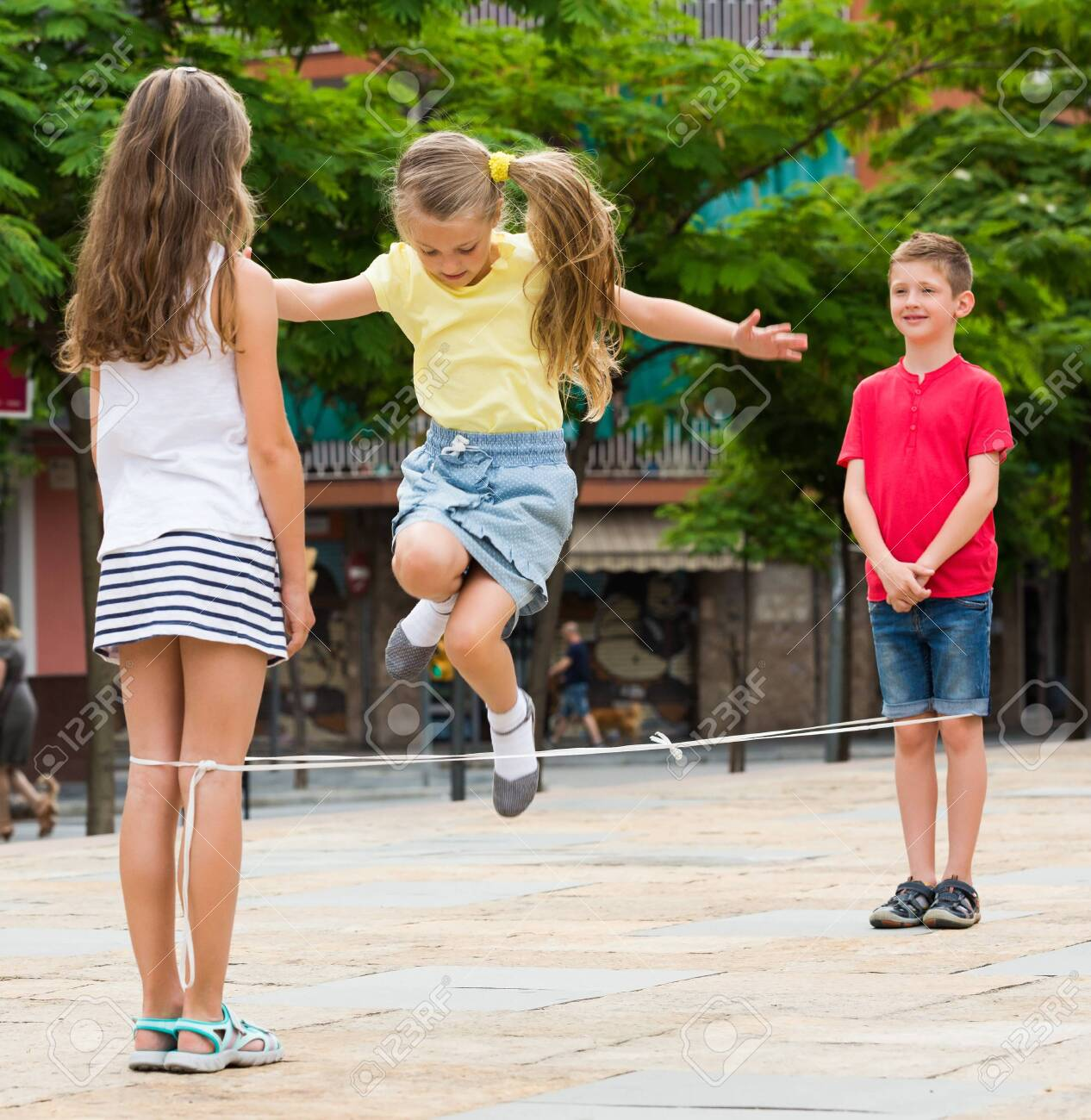 Energetic Kids Playing And Skipping On Elastic Jumping Rope In European Yard Stock Photo, Picture And Royalty Free Image. Image 124461006.