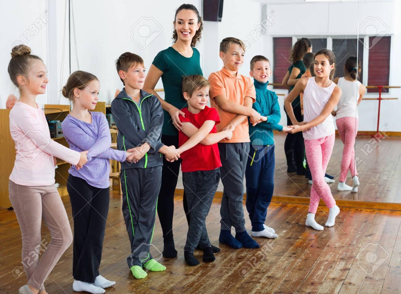 Happy positive children dancing folk dance in studio smiling and having fun - 124461037