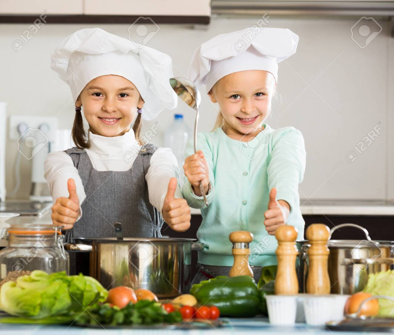 Two little american girls preparing vegetables and smiling indoors - 124547447