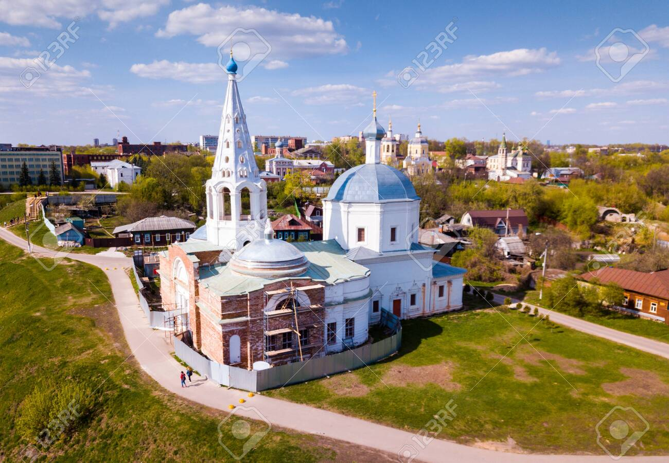 View of medieval Trinity Cathedral with typical for old Russia architecture tent-like belfry during restoration on background with picturesque Serpukhov cityscape - 124724489