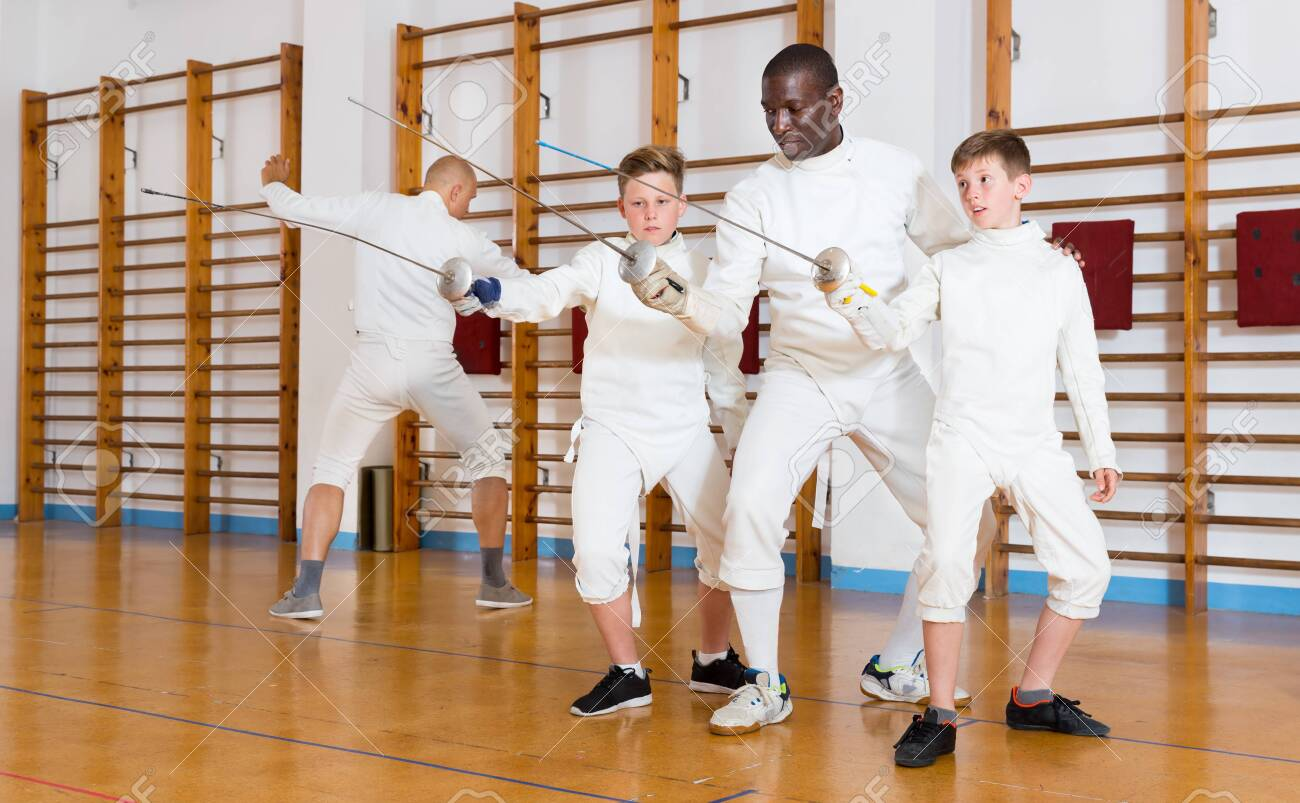 Fencing instructor explaining to young fencers effective movements