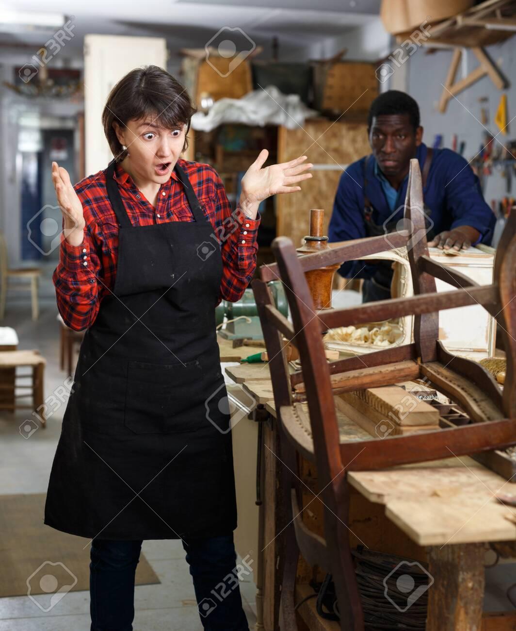 Outraged woman restorer standing near vintage armchair at workshop - 128507825
