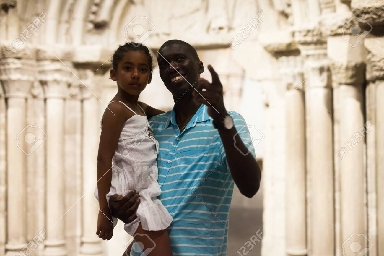 Positive Afro father and daughter looking at exhibits of medieval sculpture on exposition of museum - 128523005