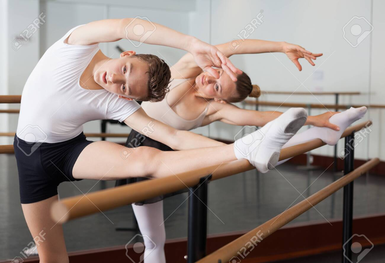 Graceful woman and young man pose in hall with ballet bar - 128645644