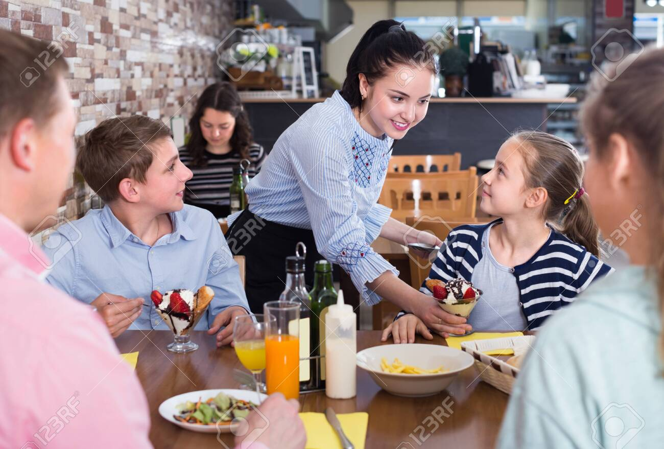 Polite nice waitress serving dishes to family in cafe - 129663123