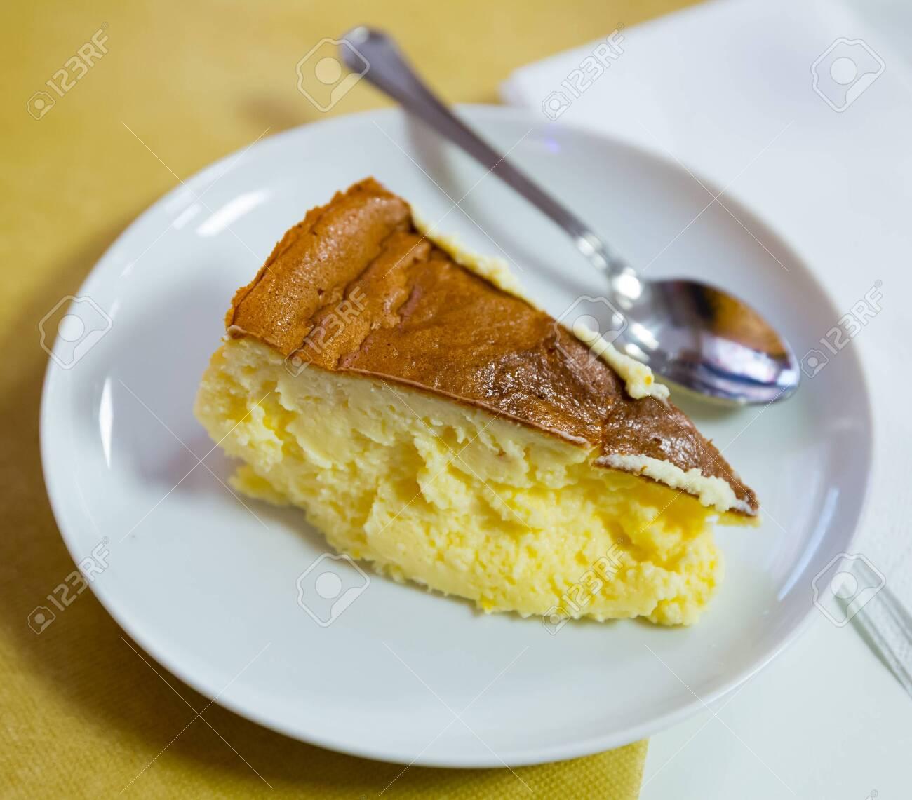 Sweet cream cheese dessert. Slice of spanish cheesecake Tarta de queso on white plate - 130048012