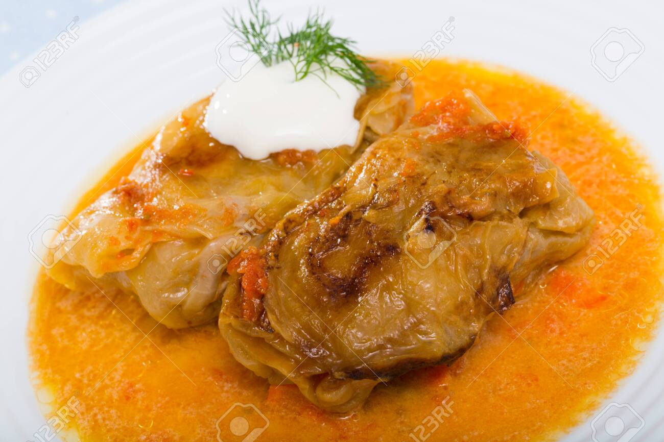Traditional dish of Balkan cuisine - stuffed cabbage leaves with fresh sour cream and herbs - 130418519