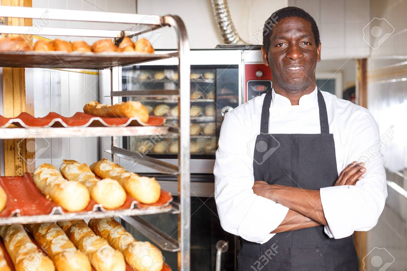 Confident baker in black apron standing with arms crossed near professional bread oven in small bakery - 130893101