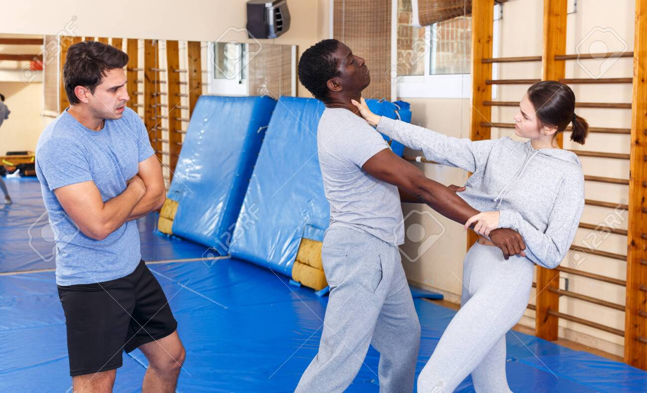 Young girl working in pair with African American man mastering new self defence moves with male coach - 133472164