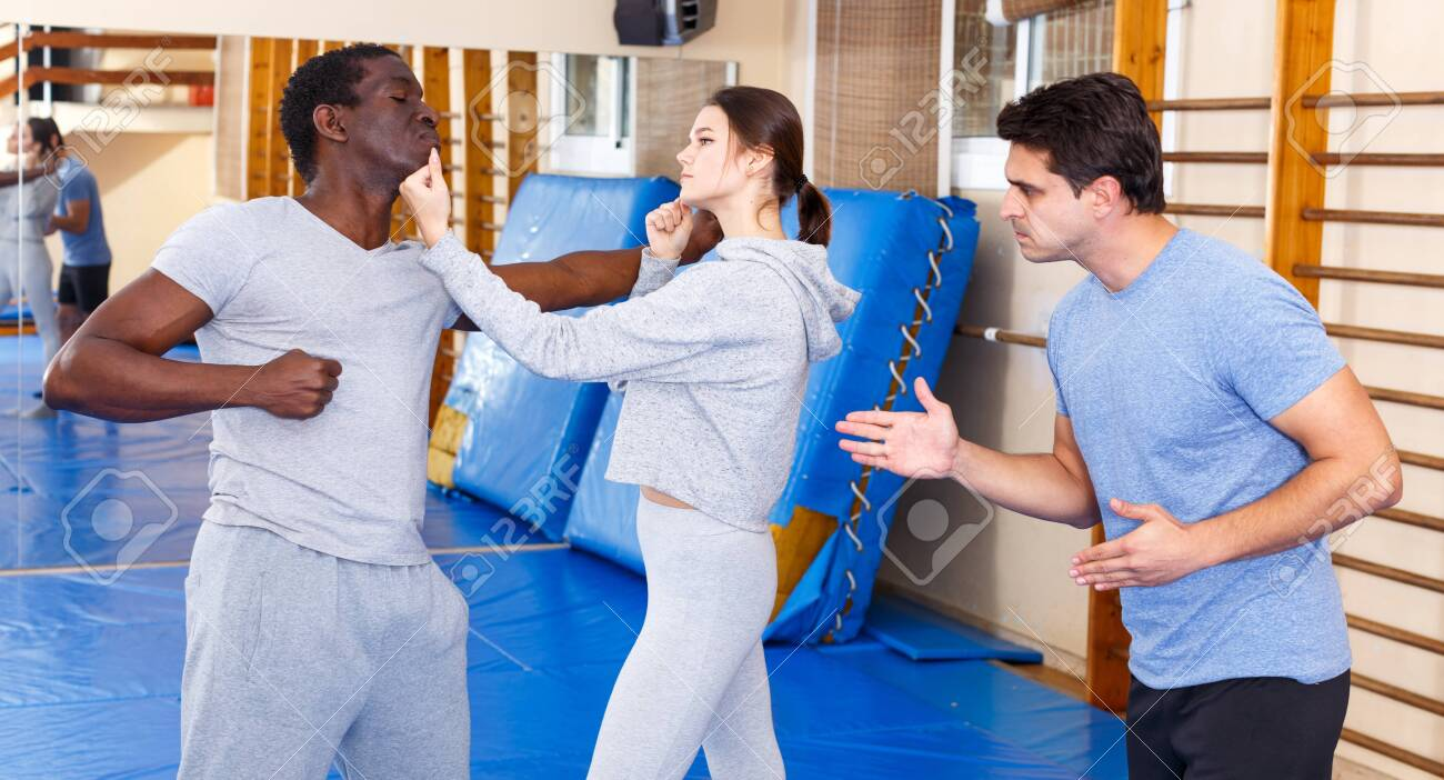Young girl working in pair with African American man mastering new self defence moves with male coach - 133472230