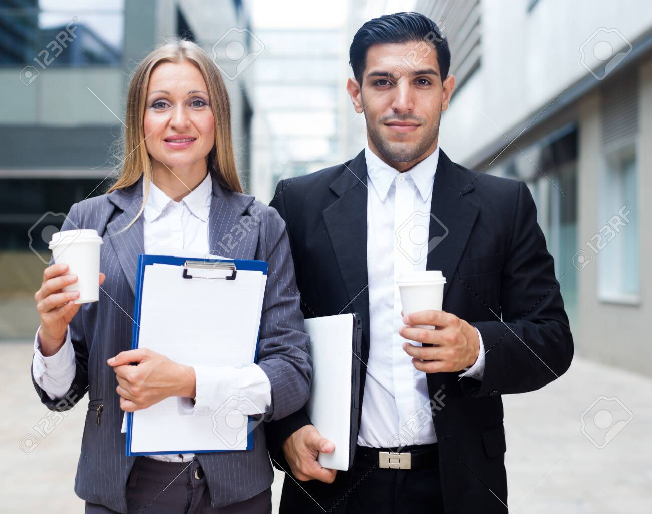 Businessman and his woman colleague in suit are standing with folder and coffee near the office. - 134554746