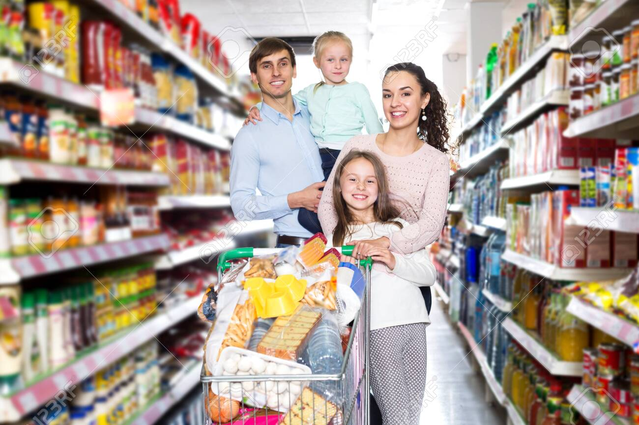 Friendly family with two daughters shopping in local supermarket - 135024313