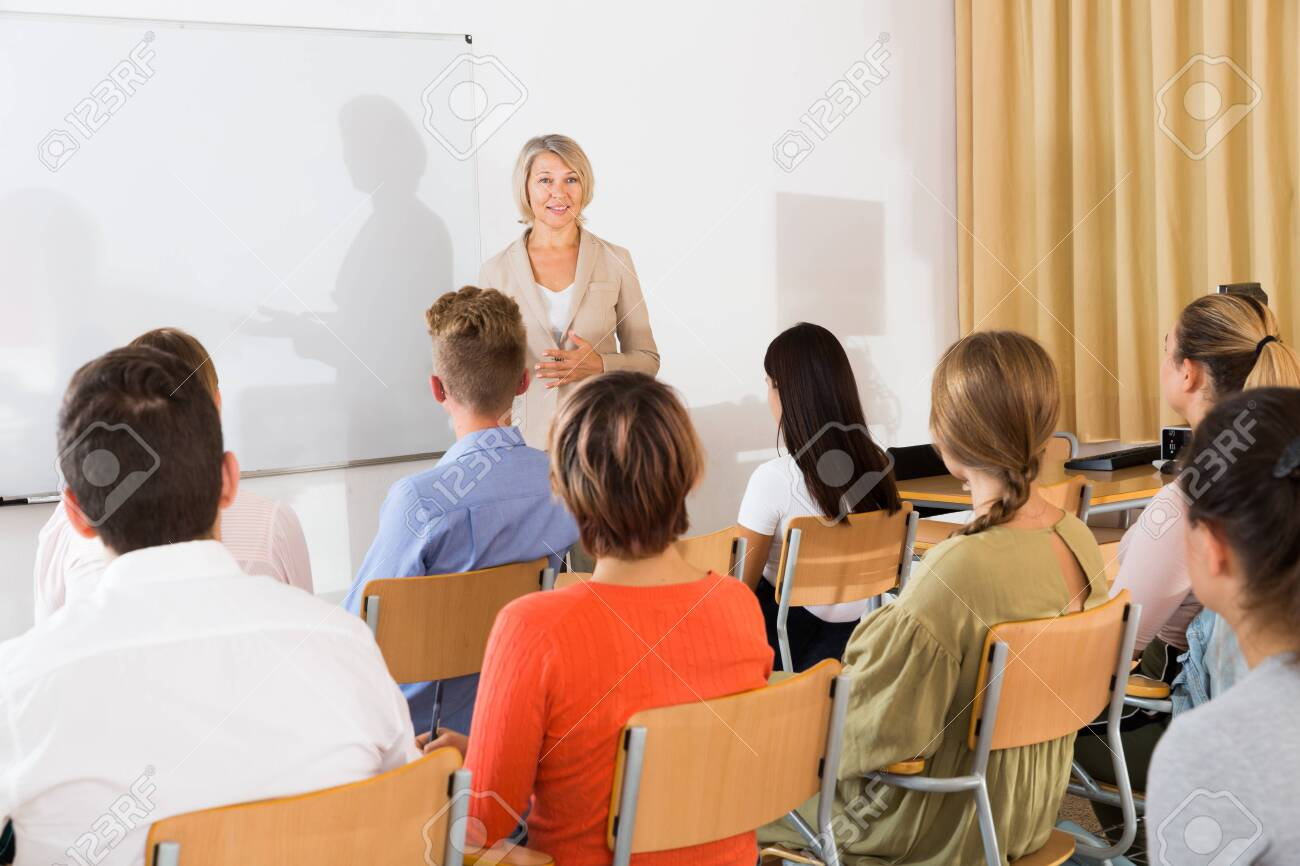 Mature female speaker giving presentation for students in lecture hall - 135803496