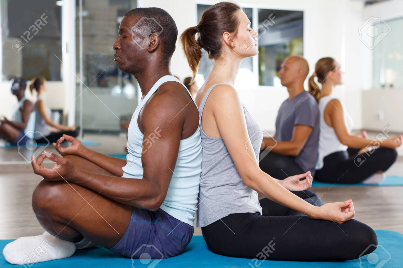Group of adult people sitting back to back in lotus positions in modern yoga studio - 135803874