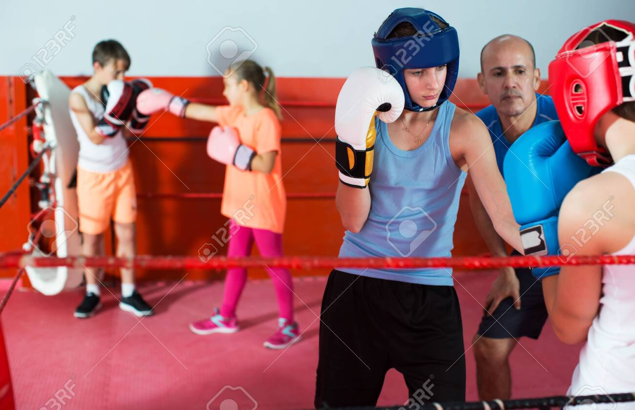 Group of children exercising with coach on boxing ring at gym - 137787119