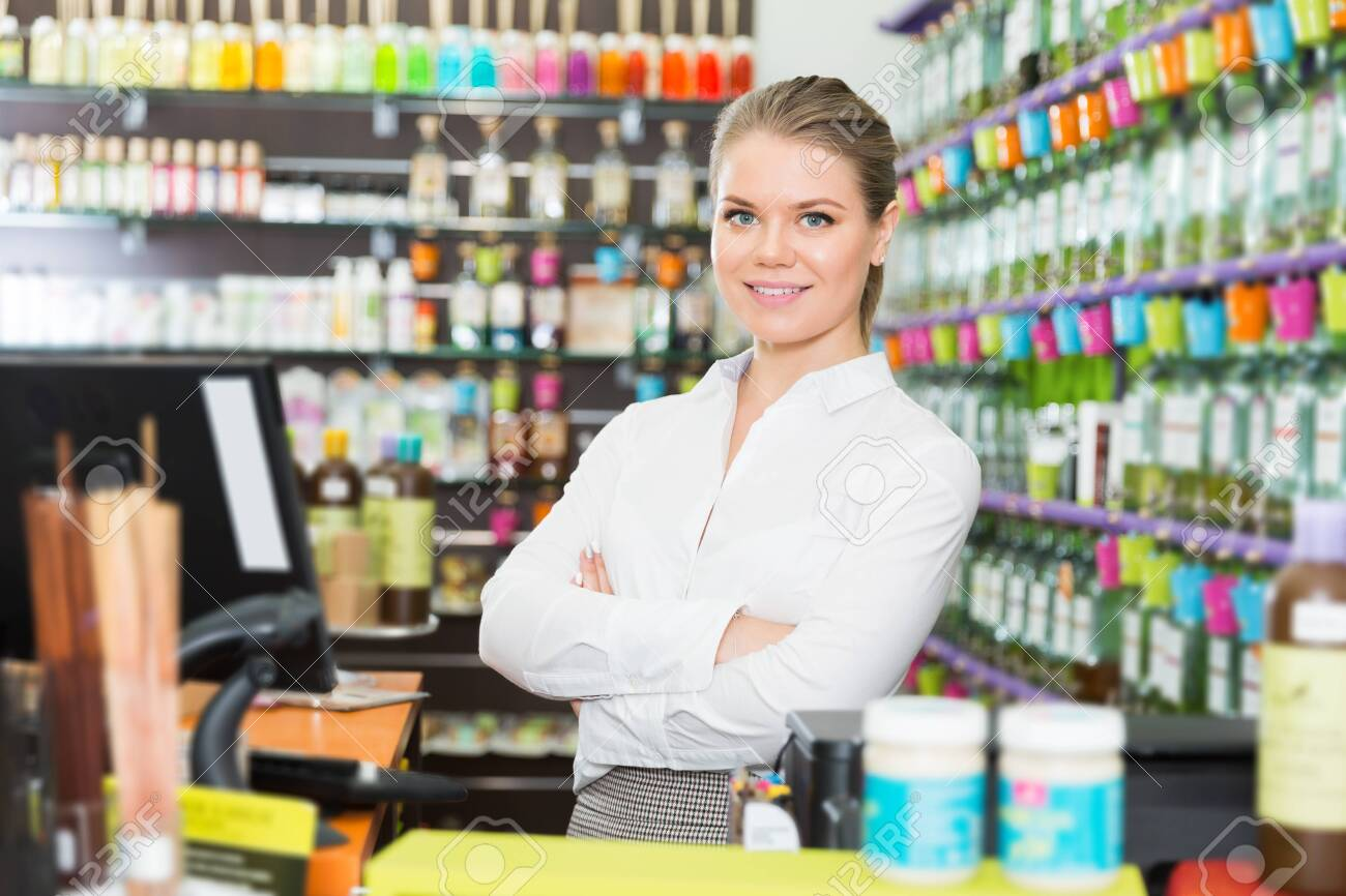 Successful happy young saleswoman standing in perfume store - 140361864