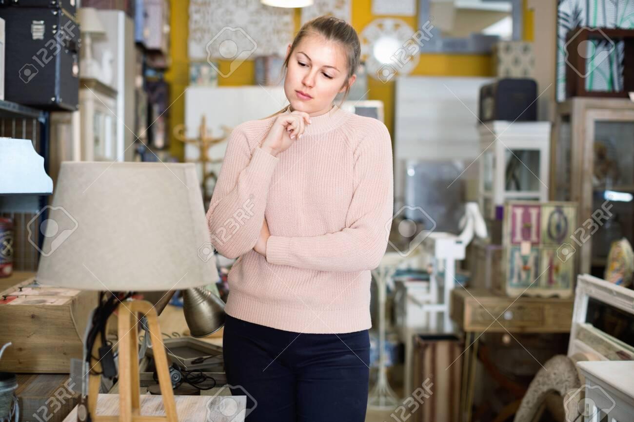 positive woman buyer standing in furniture shop choosing modern torchere indoors - 140860244