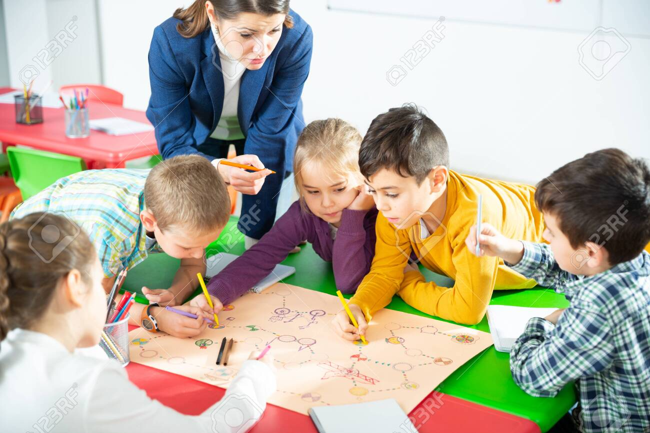 Teacher and collective of elementary age children draw together a board game - 140807919