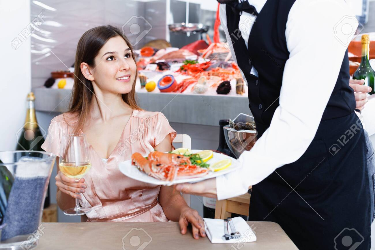 Polite waiter serving ordered seafood dishes to attractive cheerful positive girl at fish restaurant - 142538164