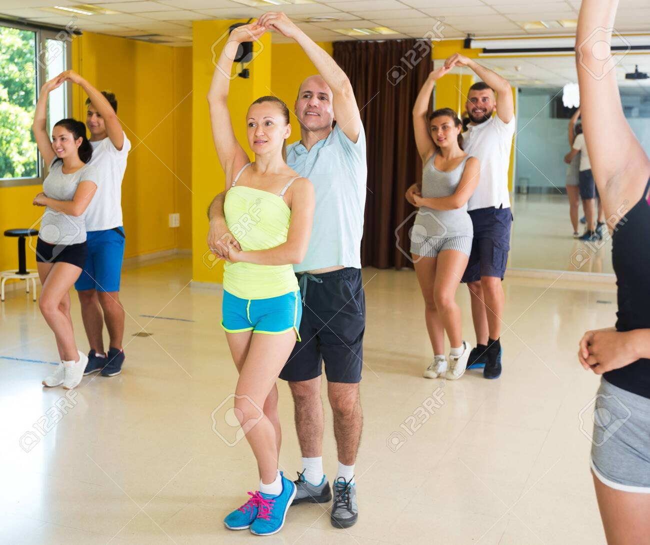 Cheerful adults dancing salsa together in dance studio - 145321576