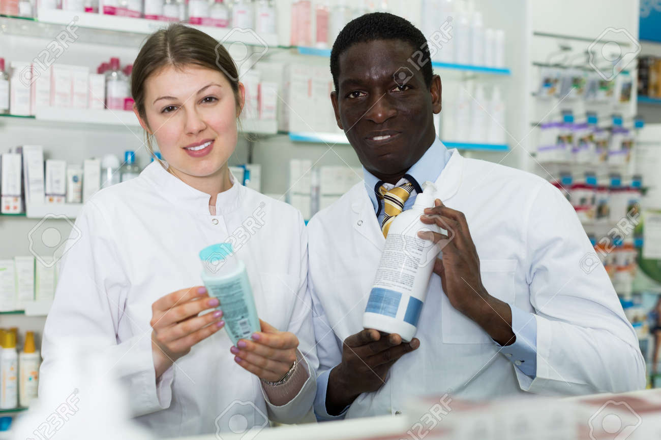 Portrait two experienced pharmacists standing in interior of modern pharmacy - 145390456