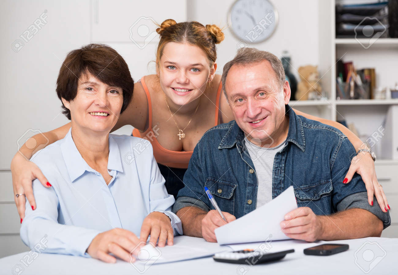 Smiling parents are reading utility bill with their adult daughter at home. - 145668973