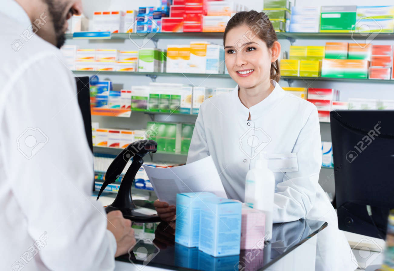 Diligent positive cheerful woman pharmacist is recommending medicine for man client in apothecary. - 147246165