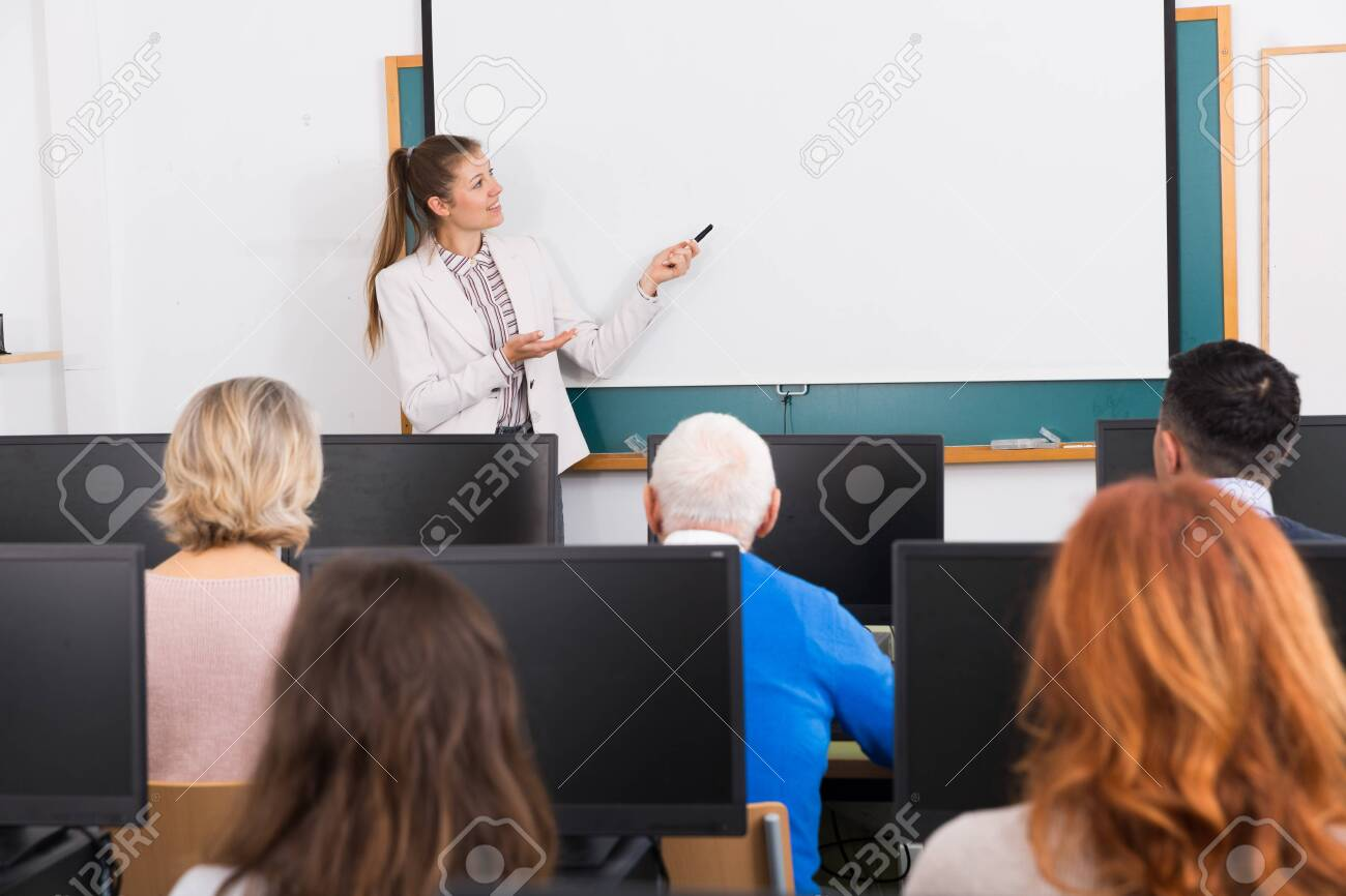 Friendly young female teacher lecturing attentive adult students of different ages in computer room - 148246005
