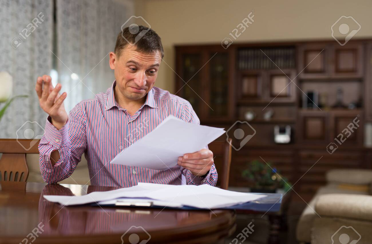Emotional man calculating domestic budget and checking accountancy at home table - 149359236