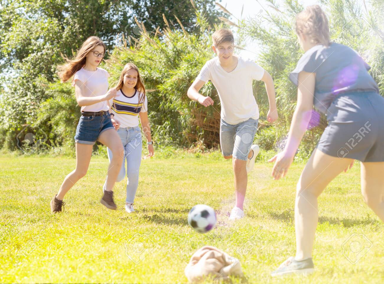 Cheerful teenagers are jogning with ball in spring park - 149849189
