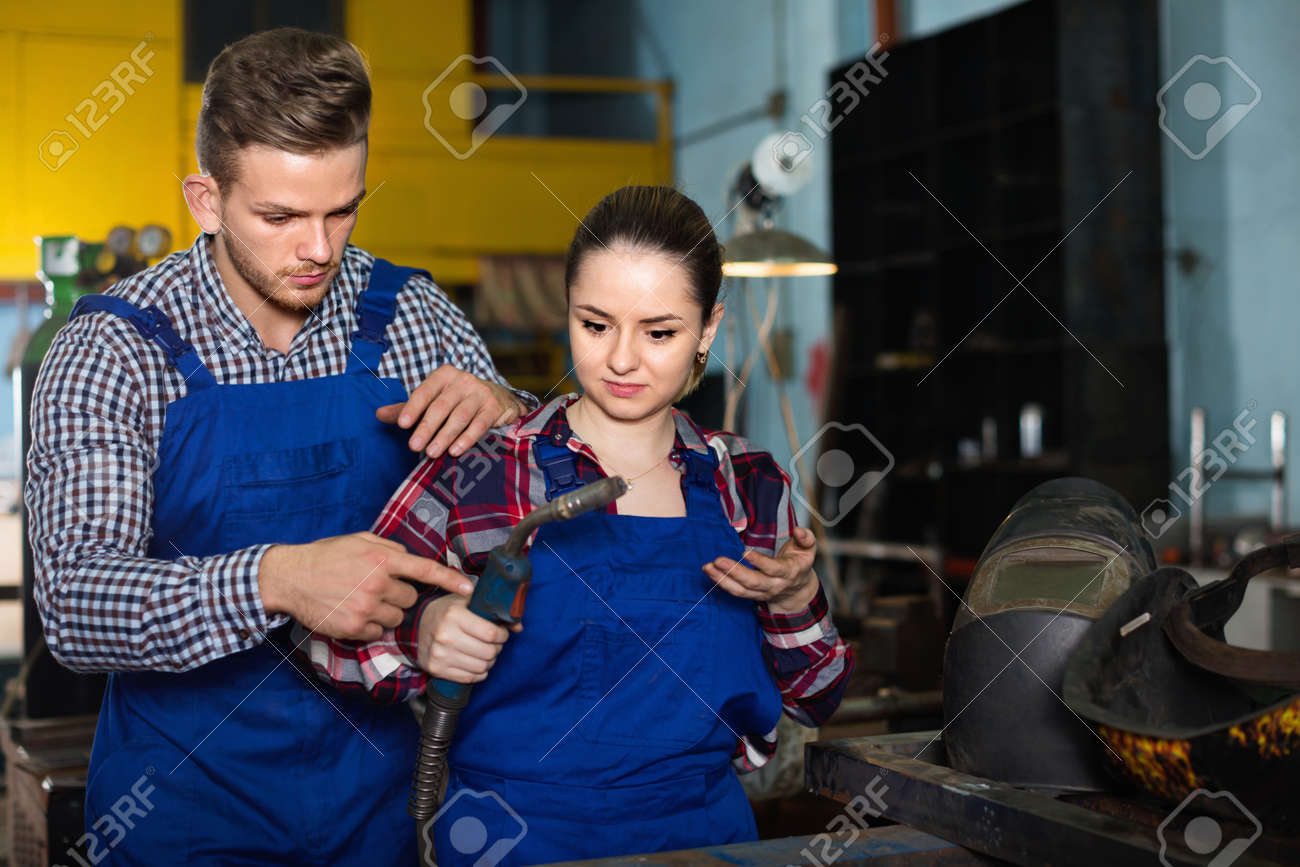 Master is educating girl to working with burning in workshop. - 151891560