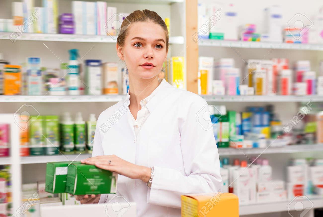Cheerful female druggist working in pharmacy - 153640375
