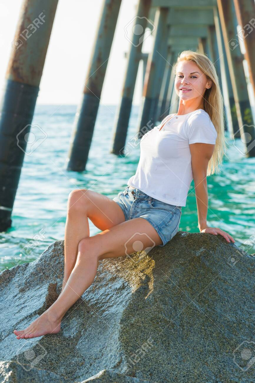 Elegant woman is resting on the rocks in her free time - 154109882