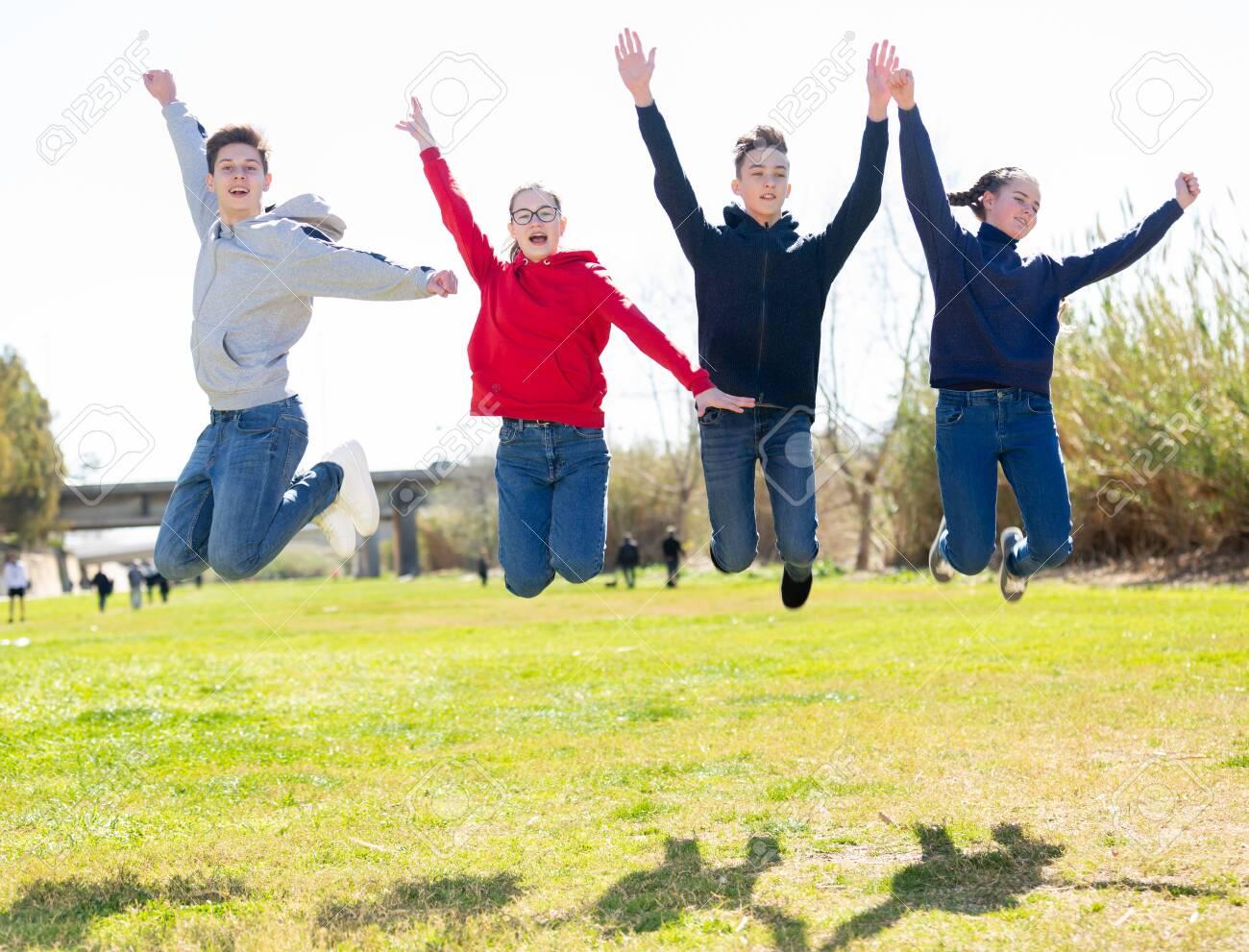 Four joyful teens jump on a lawn - 154110032