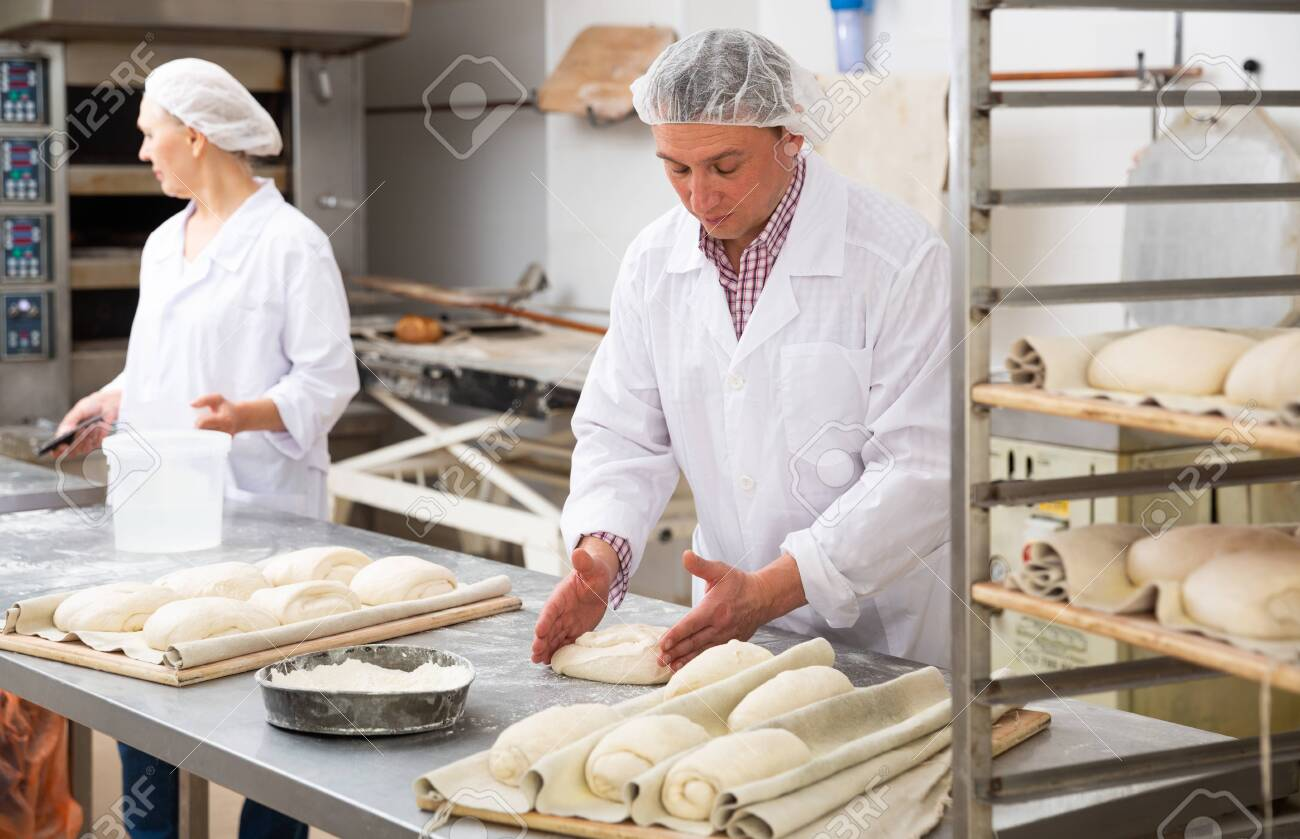 Baker forming dough for baking bread - 154475489
