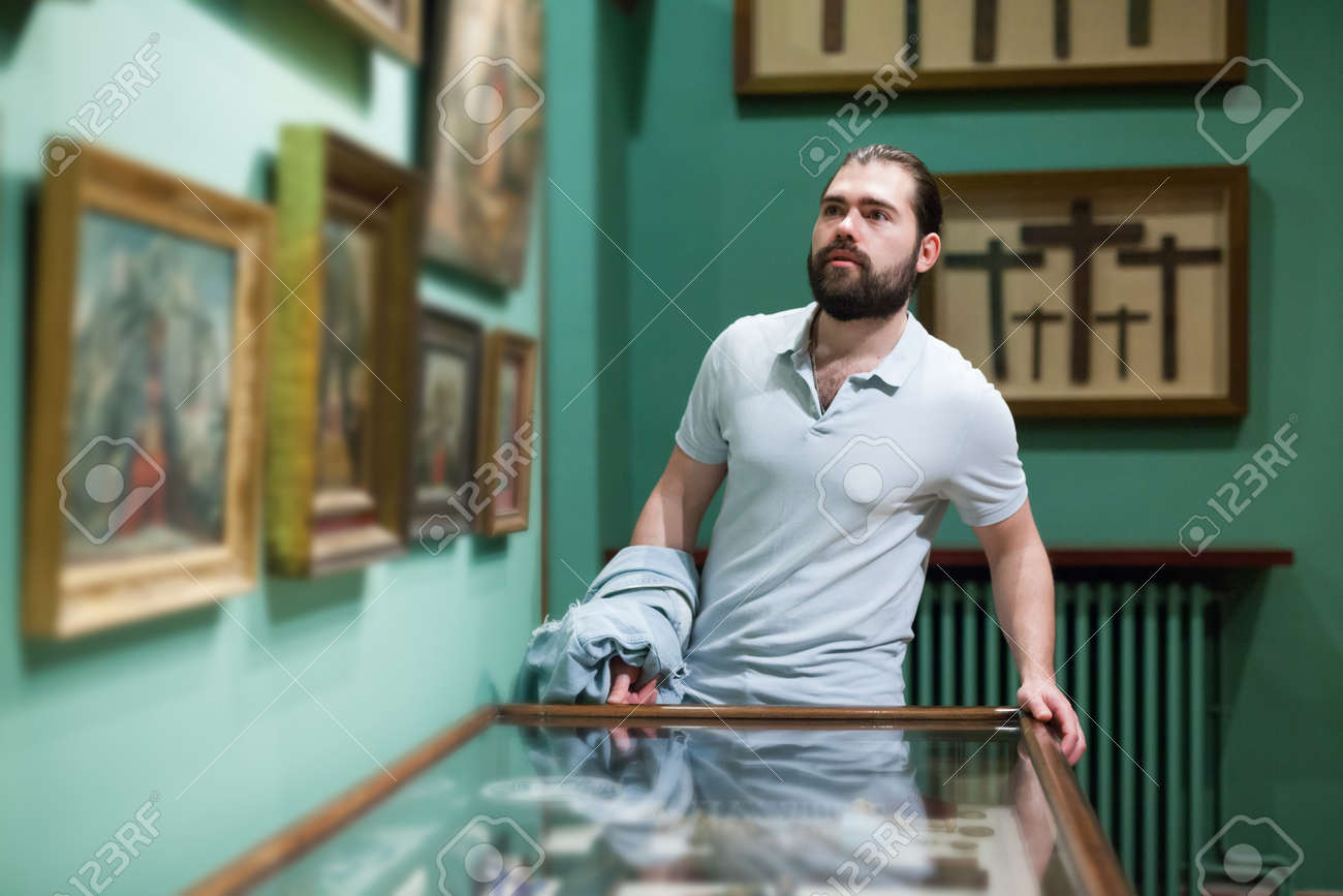 Adult man looking at exhibits in glazed stands in historical museum - 154594774