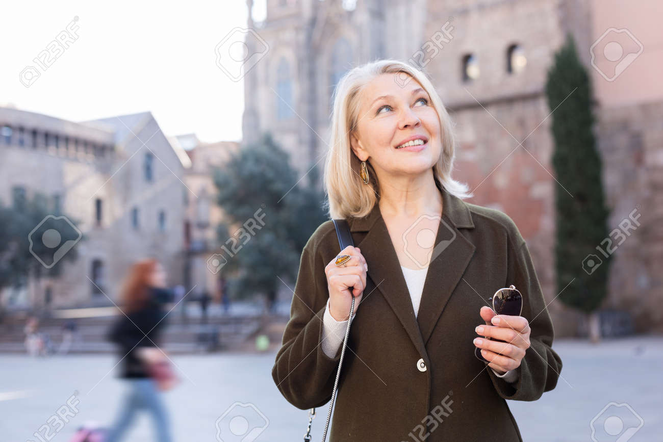 Portrait of mature cheerful woman standing on a old city street - 156255505