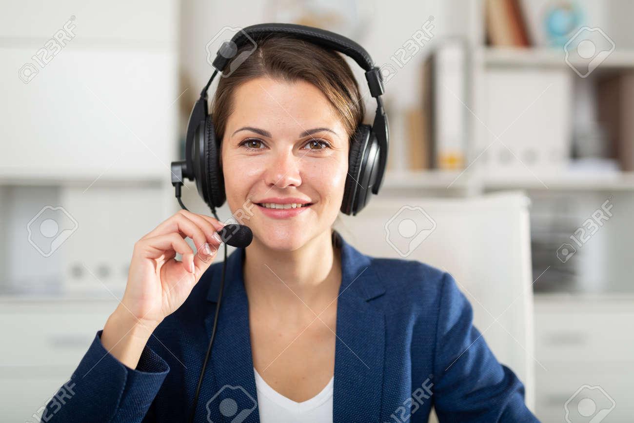 Portrait of smiling woman helpline operator with headphones - 158059773