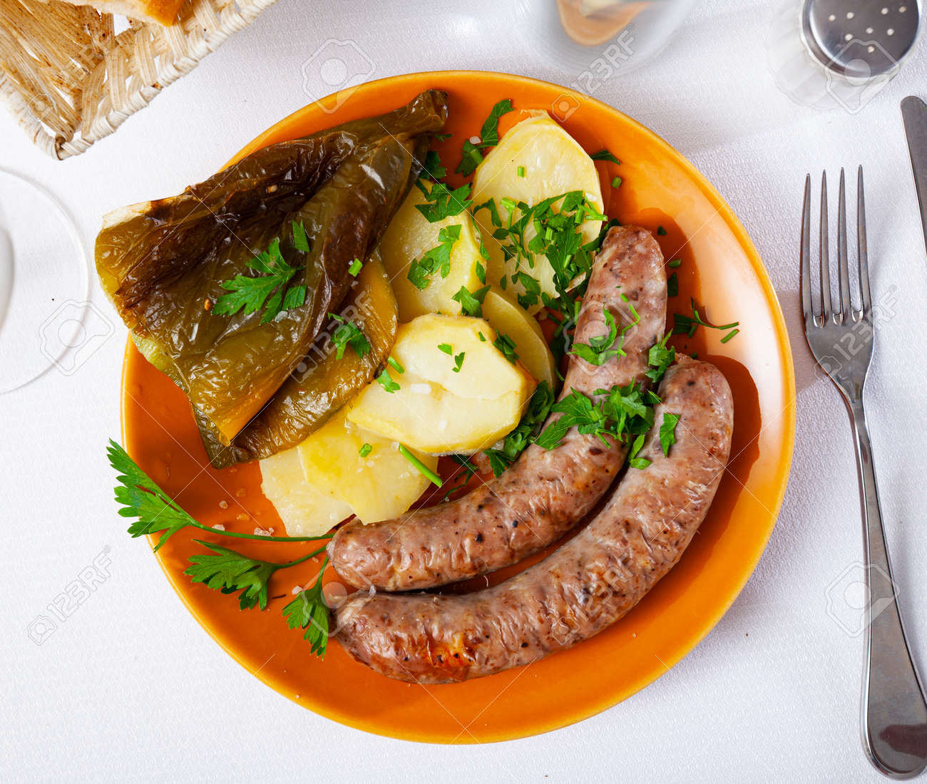 Tasty fried pork sausages with baked potatoes and pepper - 158413519