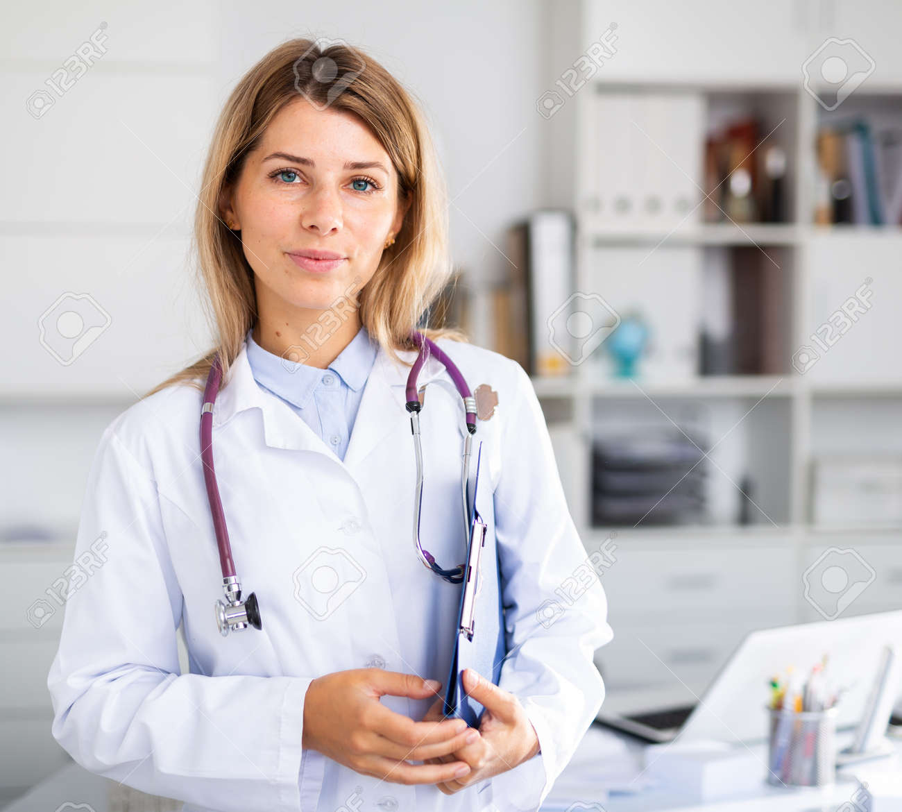 positive female doctor with stethoscope working in cabinet - 158618246